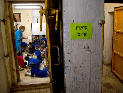 A teacher is seen distracting her class of children who took refuge in a bomb shelter as air raid sirens sound. (Photo: IDF)