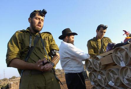 An emissary of Lubavitch wrapping tefillin on an IDF soldier on the front lines.  (Photo: UPI Photo/Debbie Hill)