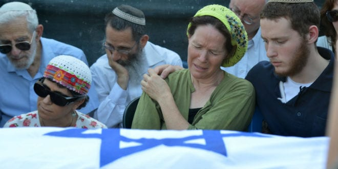 Mother of Naftali Frenkel, Rachel Frenkel, seen crying over the body of her son, during the joint funeral for the three murdered Jewish teens, in the Modiin cemetery, on July 1, 2014. The bodies of Eyal Yifrach, Gilad Sha'ar and Naftali Fraenkel were discovered the previous day in a field near Karmei Tzur in the West Bank. The three teenagers had been missing since June 12, while hitchhiking in the West Bank, and were presumed to have been abducted by terrorists. (Photo: Flash90)