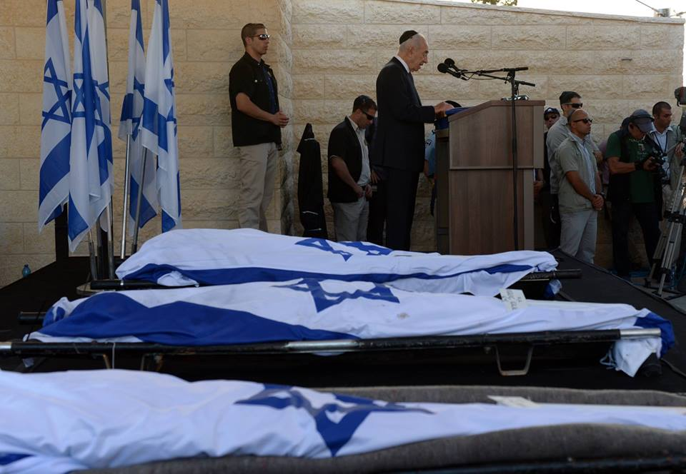 Shimon Peres eulogizes Eyal, Gilad and Naftali as their flag draped bodies rest nearby. (Photo: Official Facebook Page of Shimon Peres)