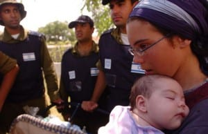 IDF soldiers accompany a mother and her child as they are relocated during the evacuation of the Israeli community Bedolach in 2005. (Photo: IDF)