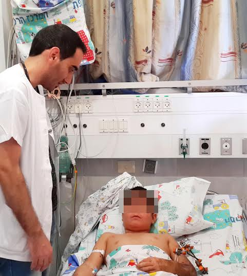 Dr. Asaf Eshbel with the 12-year-old injured in the Syrian conflict. (Photo: Ziv Medical Center)