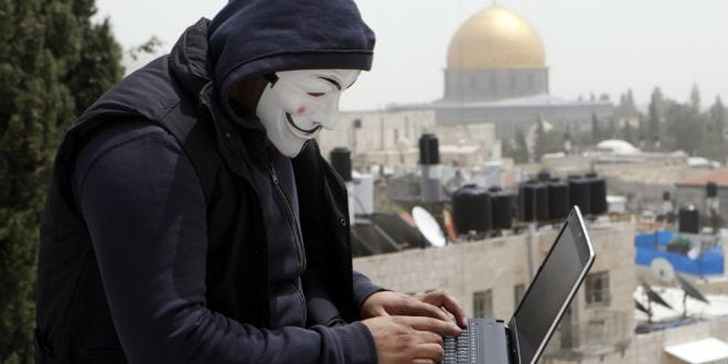 A Palestinian youth wearing masks used by computer hackers who attack a number of Israeli websites annually, seen back-dropped by the Dome of the Rock, in Jerusalem's Old City. April 08 2013. (Photo: Sliman Khader/FLASH90)