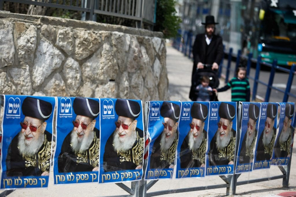 "Ultra orthodox jews walking next to a ""Shas"" party sign outside a ballots station in Jerusalem on elections day for the 20th Knesset, March 17, 2015. Photo by Nati Shohat/Flash90"