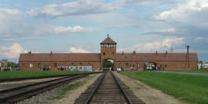 The main gate at the former Nazi concentration camp of Auschwitz II (Birkenau), and the railroad tracks leading up to it. (Photo: Michel Zacharz /Wikimedia Commons)