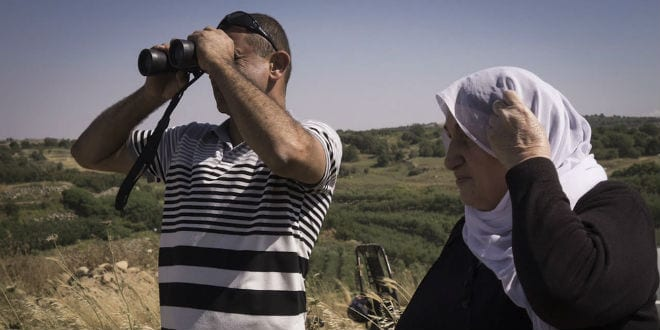 Members of the Israeli Druze community watch civil war fighting between Syrian forces from the Israeli side of the Israel-Syria border in the Golan Heights on June 16, 2015. Druze residents of Israel have recently raised concern for the safety of their fellow Druze on the Syrian side. (Photo: Basel Awidat/Flash90)