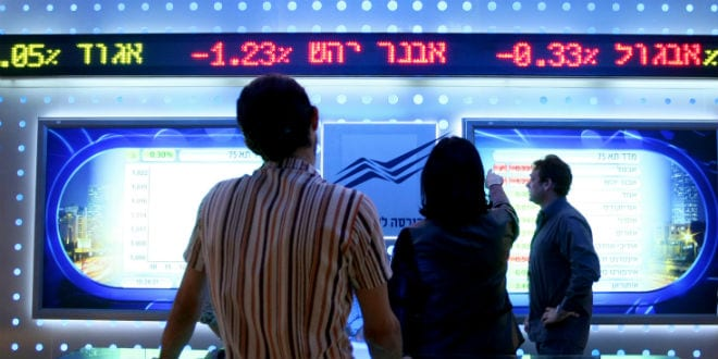 People watch a board showing stock fluctuations at the Tel Aviv stock exchange. (Photo: Moshe Shai/FLASH90)