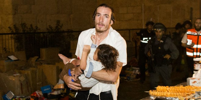 A Jewish man carries a baby injured in a stabbing attack in the Old City of Jerusalem on October 3, 2015. A Jewish family was stabbed while walking near the Lion's Gate in the Old City. The father died of his wounds. The terrorist was shot down by police. (Photo: Yonatan Sindel/Flash90)
