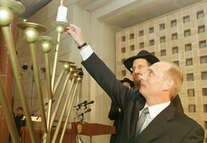 Russian President Vladimir Putin with Russia's Chief Rabbi Berl Lazar lights a menorah during the Jewish Hanukkah holiday. (Photo: Kremlin.ru/ Wiki Commons)