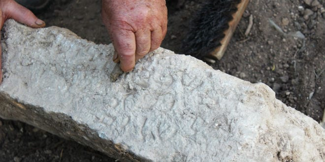 Gravestone with Inscription in Aramaic Commemorating Rabbis, Uncovered in Zippori 27.1.16 Process of cleaning the inscription. (Photo: Miki Peleg, courtesy of the Israel Antiquities Authority)