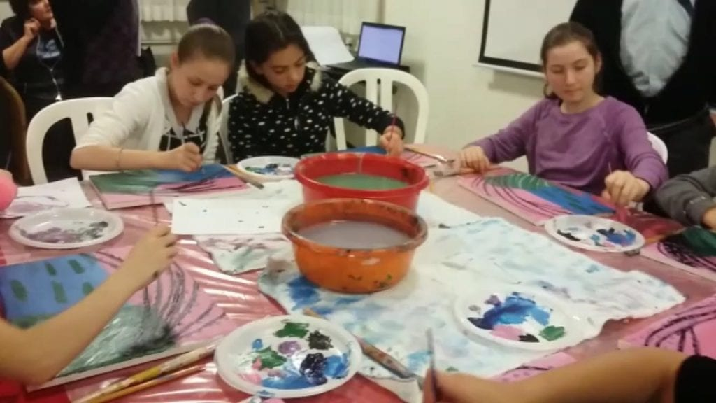 Kayla Muchnick (wearing a purple shirt) paints with children from Beit Elazraki. (Photo: Paint Party Events)