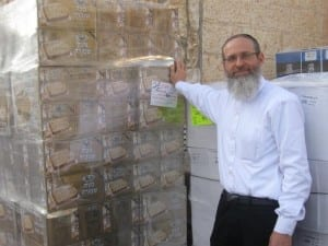 Aryeh Weingarten, Director of Karmey Chesed, stands beside a shipment of matzah which will be delivered before Passover to needy families in Israel. (Photo: Karmey Chesed)