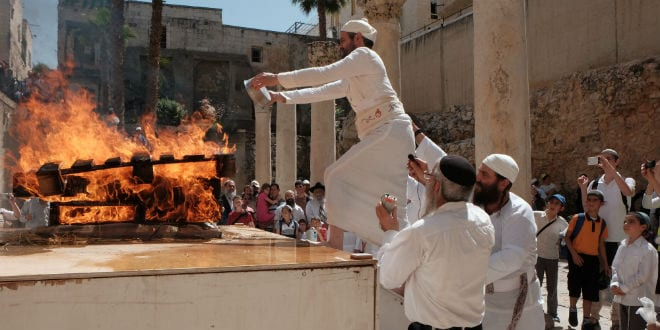 Assisted by his fellows, the priest ascends the makeshift altar and throws the Omer (barley) mixture into the fire as an offering to God. (Photo: Abba Richman)