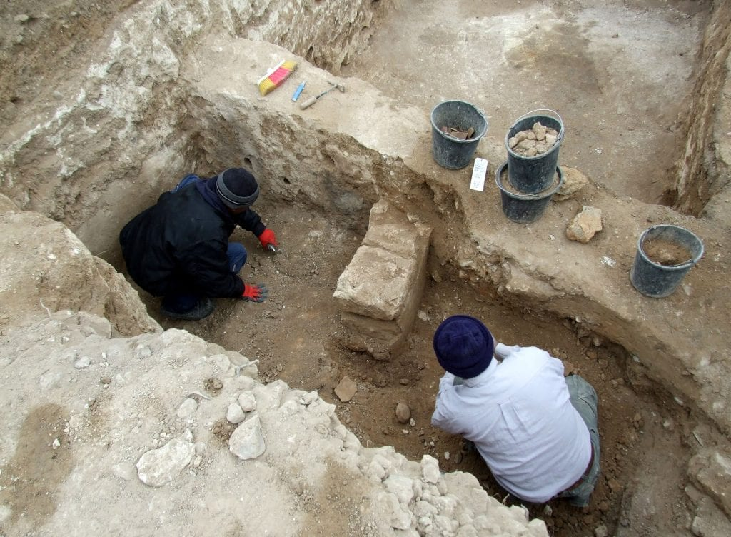 The excavation work in the gate-shrine that was exposed. The altar with its truncated horns is visible in the center of the frame. (Saʽar Ganor, Israel Antiquities Authority.)
