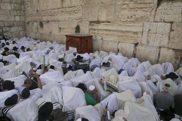 Jewish worshippers cover themselves with prayer shawls as they pray in front of the Western Wall, Judaism's holiest prayer site, in Jerusalem's Old City, during the Cohen Benediction priestly blessing at the Jewish holiday of Sukkot, October 19, 2016. (Photo by Yonatan Sindel/Flash90)