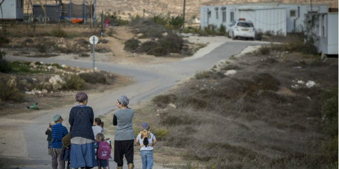 Jewish residents of the unauthorized Israeli outpost of Amona, in the West Bank, seen walking on the streets of the outpost on November 17, 2016.  (Miriam Alster/Flash90)